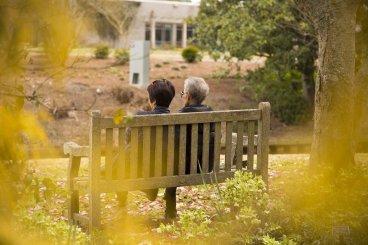 Zwei Senioren sitzen in einem Park auf einer Bank.